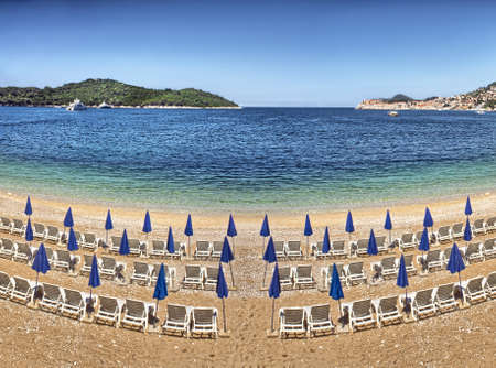 Sunshades and blue deck chairs on beach at Dubrovnik - Croatia