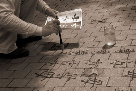 Man painting Mandarin characters in water on brick stones in a park in Shanghai, China