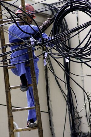 Telephone repairman on ladder adjusting coiled cables