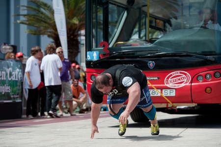CANARY ISLANDS – SEPTEMBER 03: Warrick Brant from Australia pulling a double-decker bus behind himself during Strongman Champions League in Las Palmas September 03, 2011 in Canary Islands, Spain Stock Photo - 10515410