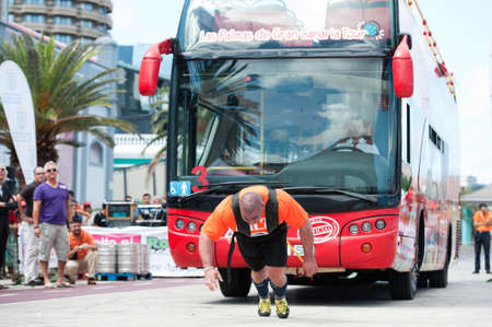CANARY ISLANDS – SEPTEMBER 03: Ervin Katona from Serbia pulling a double-decker bus behind himself during Strongman Champions League in Las Palmas September 03, 2011 in Canary Islands, Spain Editorial