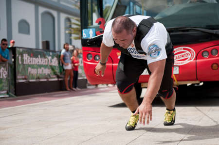 CANARY ISLANDS – SEPTEMBER 03: Akos Nagy from Hungary pulling a double-decker bus behind himself during Strongman Champions League in Las Palmas September 03, 2011 in Canary Islands, Spain