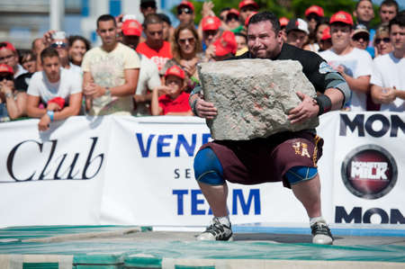 CANARY ISLANDS – SEPTEMBER 03: Alex Curletto from Italy lifting a heavy stone during Strongman Champions League in Las Palmas September 03, 2011 in Canary Islands, Spain