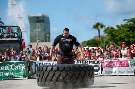 CANARY ISLANDS - SEPTEMBER 03: Alex Curletto from Italy lifting and rolling a wheel (weights 400kg) 8 times during Strongman Champions League in Las Palmas September 03, 2011 in Canary Islands, Spain Stock Photo - 10559056