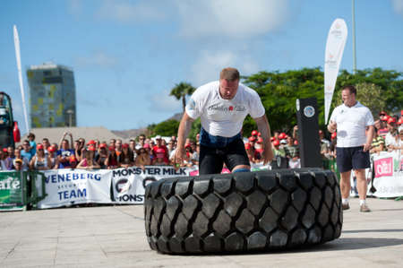 CANARY ISLANDS - SEPTEMBER 03: Lauri Nami (m) from Estonia lifting and rolling a wheel (weights 400kg) 8 times during Strongman Champions League in Las Palmas September 03, 2011 in Canary Islands, Spain
