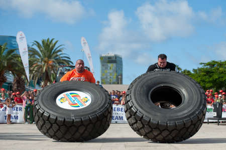 CANARY ISLANDS-SEPTEMBER 3: Ervin Katona (l) from Serbia and Arno Hams from Holland (r) lifting a wheel during Strongman Champions League in Las Palmas September 03, 2011 in Canary Islands, Spain  Editorial