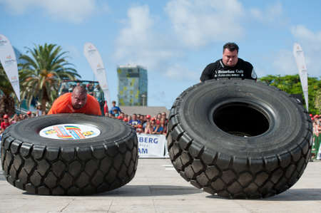 CANARY ISLANDS-SEPTEMBER 3: Ervin Katona (l) from Serbia and Arno Hams from Holland (r) lifting a wheel during Strongman Champions League in Las Palmas September 03, 2011 in Canary Islands, Spain  Stock Photo - 10559060