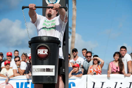 CANARY ISLANDS - SEPTEMBER 03: Julio Jimenez Zancajo from Spain lifting a heavy trash can for longest possible time during Strongman Champions League in Las Palmas September 03, 2011 in Canary Islands, Spain  Stock Photo - 10559041