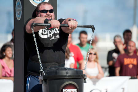 CANARY ISLANDS - SEPTEMBER 03: Warrick Brant from Australia lifting a heavy trash can for longest possible time during Strongman Champions League in Las Palmas September 03, 2011 in Canary Islands, Spain  Stock Photo - 10559038