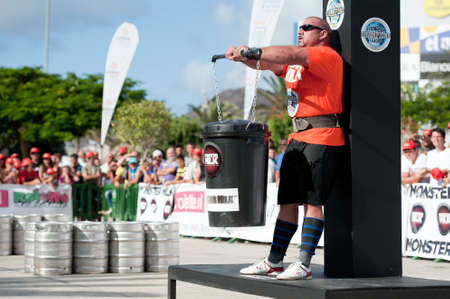 CANARY ISLANDS - SEPTEMBER 03: Ervin Katona from Serbia lifting a heavy trash can for longest possible time during Strongman Champions League in Las Palmas September 03, 2011 in Canary Islands, Spain  Stock Photo - 10559048