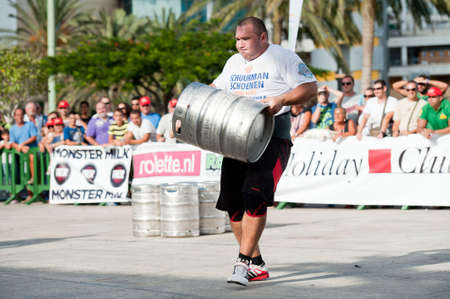 CANARY ISLANDS - SEPTEMBER 03: Julio Jimenez Zancajo from Spain lifting and running with a heavy barrel during Strongman Champions League in Las Palmas September 03, 2011 in Canary Islands, Spain