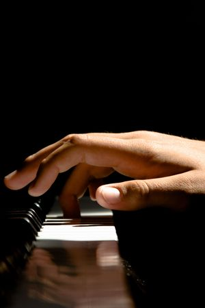 piano: A Caucasian male�s hand playing a piano in dramatic lighting