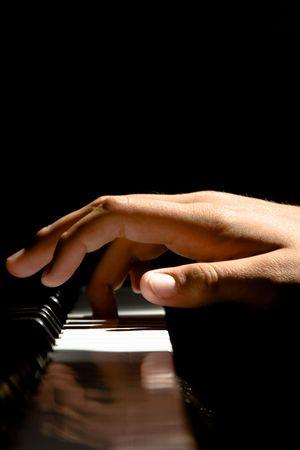 fortepian: A Caucasion mężczyźni strony odgrywa fortepian dramatyczne oświetlenie Zdjęcie Seryjne