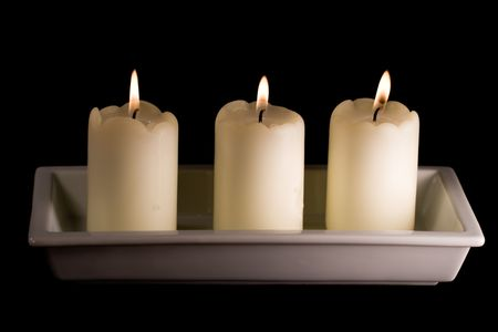 Three white candles lined up in a white saucer isolated on black Zdjęcie Seryjne