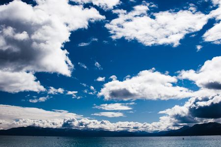 expanse: a deep blue sky with dramatic white clouds over Lake Tahoe Stock Photo
