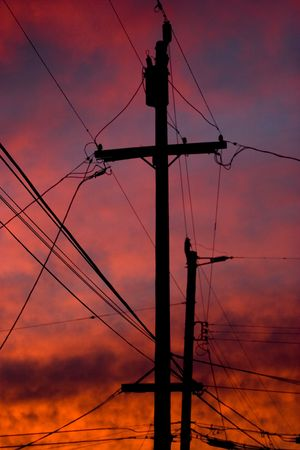 telephone poles: Telephone poles and wires against a dramatic orange sunset Stock Photo