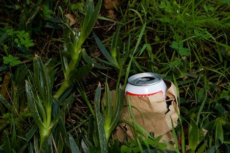 A beer can in a paper bag on the ground Stock Photo