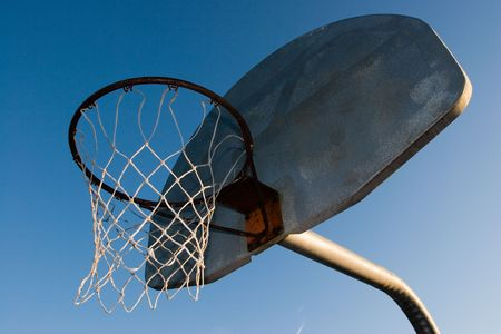 A rusty old basketball hoop against a blue sky in the evening. photo