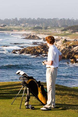 teen golf: Un jugador de golf se encuentra en Chipre Punto con el campo de golf Pebble Beach hermoso litoral detr�s de �l