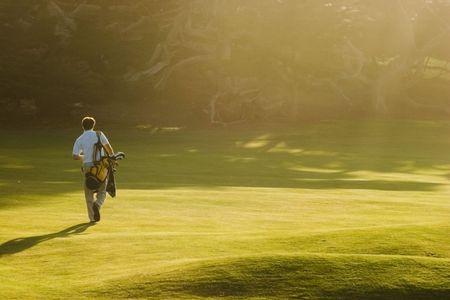 A golfer walks on a golf course as sunbeams stream through the trees.