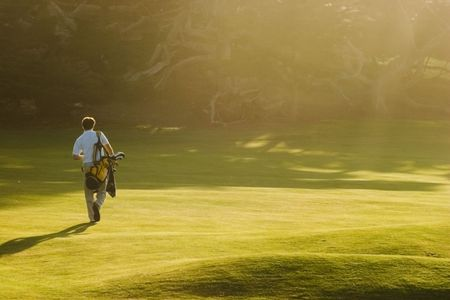 A golfer walks on a golf course as sunbeams stream through the trees. photo