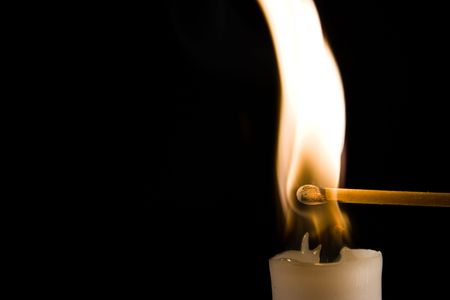 a match being ingited by a burning candle photo