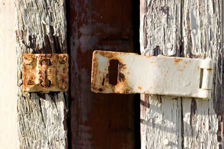 A rusted metal latch with peeling white paint Stock Photo - 429267
