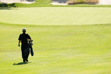 A golfer walks towards the green Stock Photo - 429278