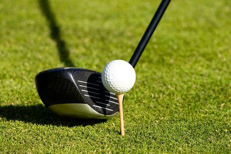 golf club next to a ball on a tee photo