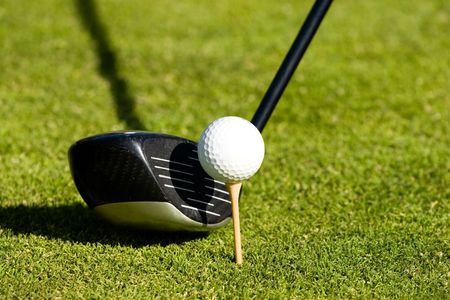 cut the competition: golf club next to a ball on a tee Stock Photo