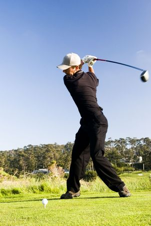 A young man tees off (motion blur) photo