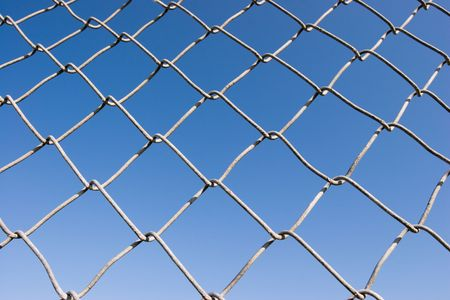 exclude: Closeup of a chin link fence with blue sky in the background