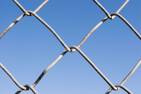 Closeup of a chin link fence with blue sky in the background photo