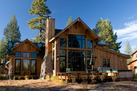 a large cabin in the mountains surrounded by trees photo