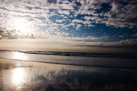 expansive: an expansive beach with small waves and a dramatic deep blue sky with clouds