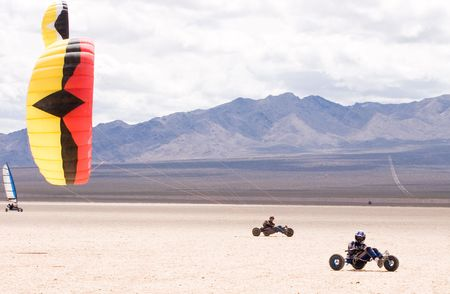 Two kite buggy pilots ride across a dry lakebed Stock Photo
