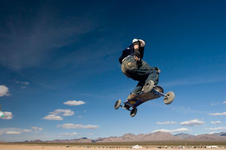 A mountainboarder in mid air with a deep blue sky and desert in the background Stock Photo - 429227