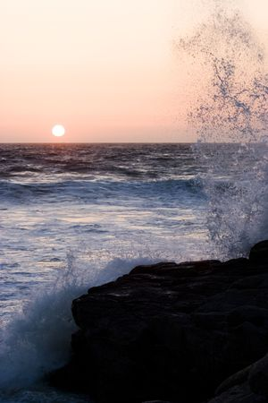 wind force: A wave crashes on a rock at sunset