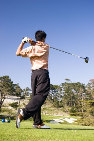 A young man follows through after teeing off photo