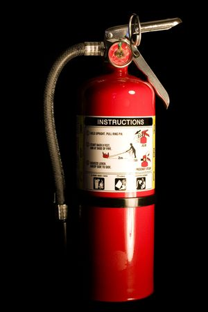 fire extinguisher: A red fire extinguisher isolated on a black background Stock Photo
