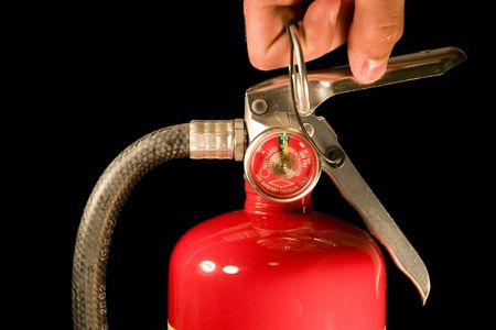workplace safety: A hand pulls the pin on a red fire extinguisher