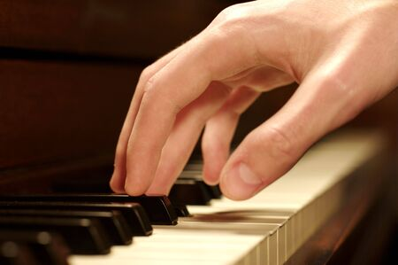 tune: A Caucasian males hand playing a piano in dramatic lighting