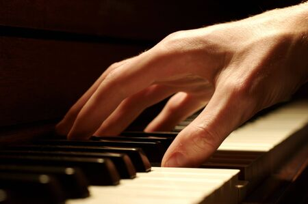piano closeup: A Caucasian males hand playing a piano in dramatic lighting