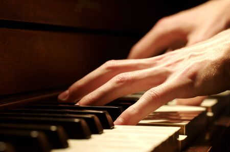 playing piano: A Caucasian males hand playing a piano in dramatic lighting
