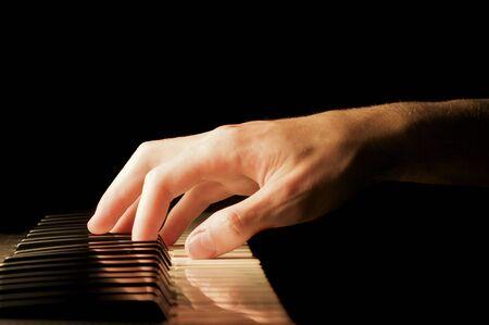 keyboard: A caucasian males hand playing a keyboard