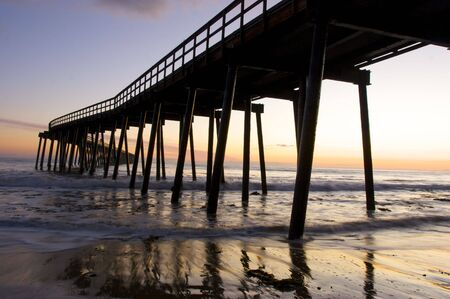 wood pillars: A Pier silhouetted at sunset Stock Photo