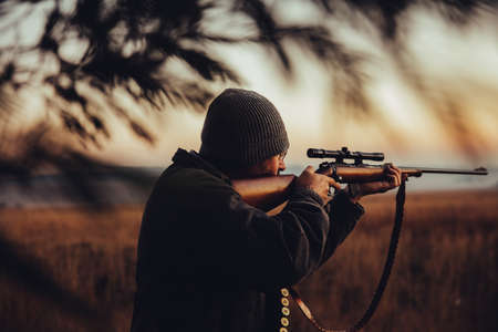 pointing gun: hunter observing on field and pointing gun to his prey Stock Photo
