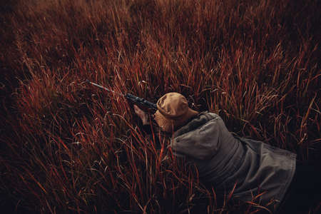 high angle view: High angle view of Hunter laying in high red grass with rifle aiming on prey Stock Photo