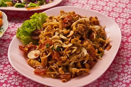 Spicy fried fish, fried squid and cashew nut salad in dish ready for eat