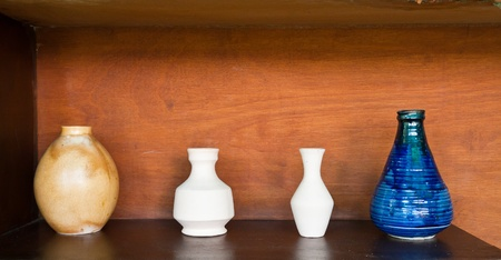 four earthenwares on wooden shelf in still-life style photo